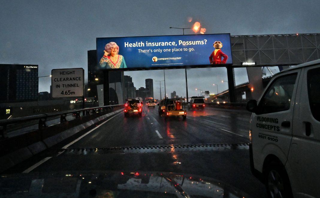 21 maggio 2020, Melbourne. I pendolari guidano sotto un cartellone di un'assicurazione sanitaria. Il gruppo di assicurazione sanitaria statunitense Mercer afferma che diversi clienti stanno cercando di trattare i non vaccinati come se fossero a rischio per la salute quanto i fumatori con un supplemento di 50 dollari al mese.(Immagine: WILLIAM WEST/AFP tramite Getty Images)