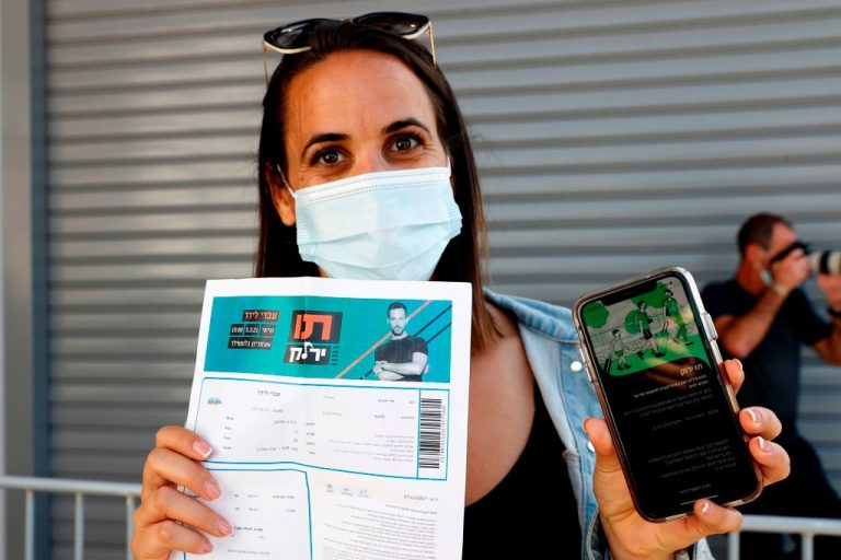 In March, a woman showed off her Green Pass vaccine passport to promote vaccine acceptance to the public upon arrival at Bloomfield Stadium in Tel Aviv. On Aug. 29, the Israeli government announced Green Pass status will expire six months after the last injection, ushering in an era of mandatory acceptance of cyclical boosters of the mRNA and adenovirus vector gene-therapy-based COVID-19 vaccines.