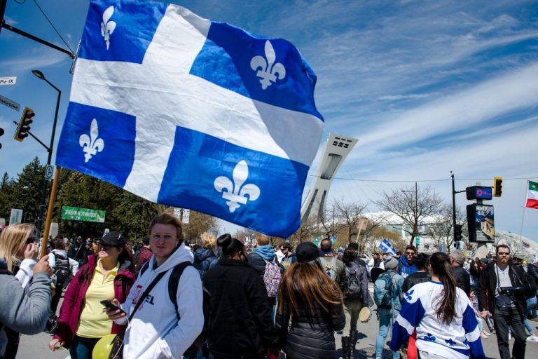 Demonstrators march past the Olympic Stadium in a protest against mandatory masks and curfews in May of 2021. As many as 100,000 Quebec residents hit the streets of downtown Montreal to protest Canada's first vaccine passport mandate.