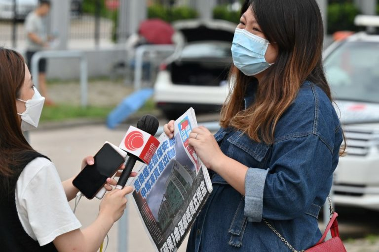 A local television crew interview a supporter outside the Next Media and Apple Daily headquarters in Hong Kong on June 22, 2021 as the embattled pro-democracy newspaper Apple Daily has been hit by a wave of resignations as authorities push to see the outspoken tabloid silenced.