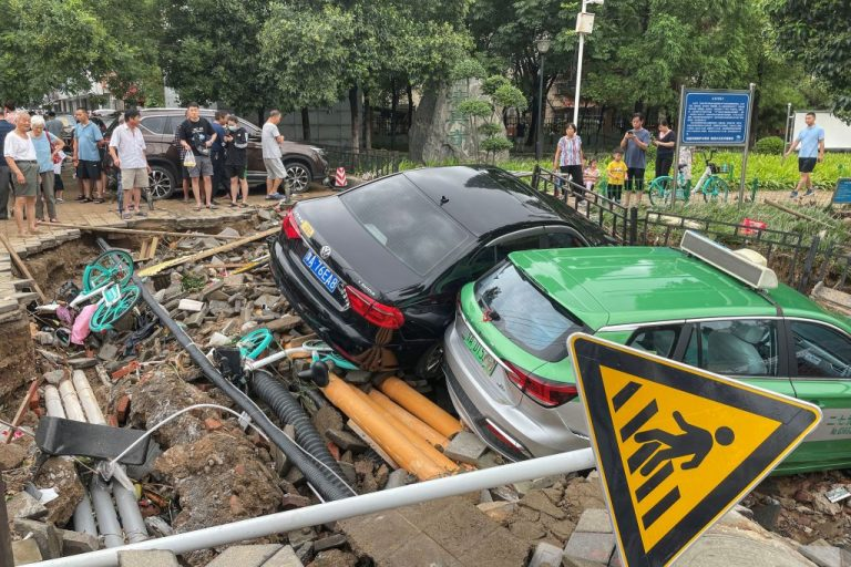 Damaged cars rest on debris after heavy rains hit the city of Zhengzhou causing floods in China's central Henan province on July 21, 2021.