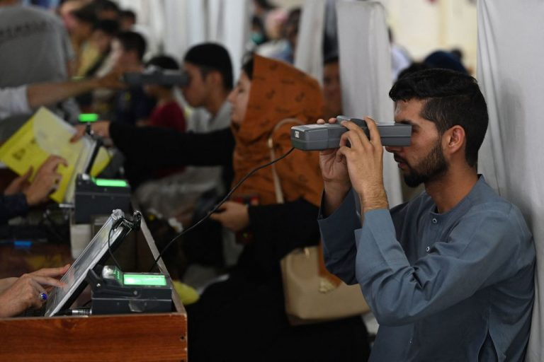 A man looks through an optical biometric reader to submit his passport application at an office in Kabul on July 25, 2021. Scanners and a database of at least 25 million people's biometric data have fallen into the Taliban's hands and are being used to hunt NATO-friendly Afghans.