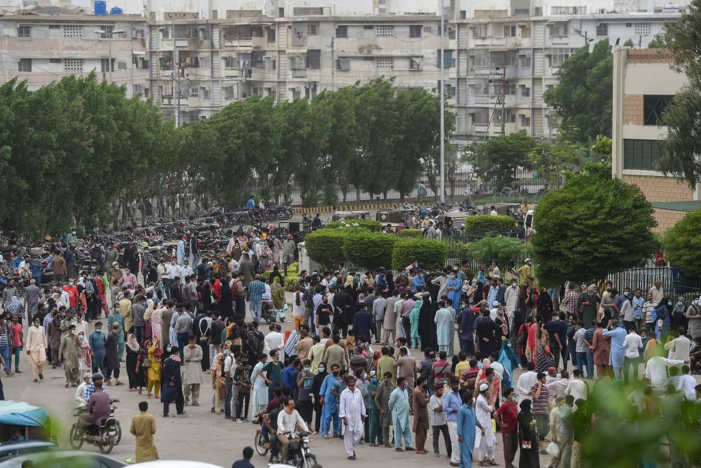 La gente si riunisce in gran numero per ricevere un'iniezione di SARS-CoV-2 in un centro di vaccinazione a Karachi, il 29 luglio 2021. I cittadini della provincia del Sindh che rifiutano di vaccinarsi rischiano di perdere il servizio di telefonia mobile e il diritto al lavoro. (Immagine: ASIF HASSAN/AFP tramite Getty Images)