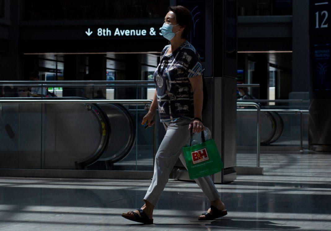 Una donna che indossa una maschera per il viso cammina attraverso la stazione Penn di New York il 2 agosto 2021. Il sindaco di New York Bill de Blasio ha smesso di ordinare un mandato di maschera in città lunedì, ma ha emesso una forte raccomandazione a tutti i newyorkesi di indossare mascherine in ambienti interni pubblici. (Immagine: KENA BETANCUR/AFP via Getty Images)