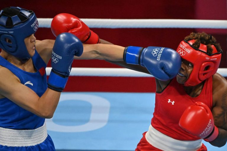USA's Oshae Lanae Jones (red) and China's Gu Hong fight during their women's welter (64-69kg) semi-final boxing match during the Tokyo 2020 Olympic Games at the Kokugikan Arena in Tokyo on August 4, 2021.