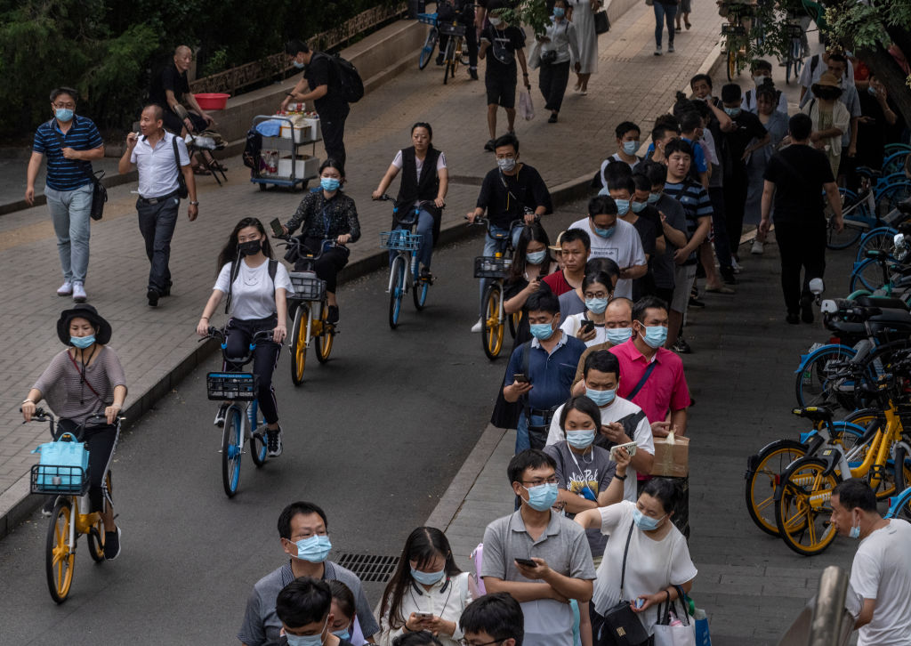 PECHINO, CINA, 4 agosto 2021: Nella foto dei pendolari, molti dei quali indossano maschere per proteggersi dal COVID-19. Da mesi la Cina sta combattendo il suo peggior focolaio di COVID-19, dopo che i lavoratori dell'area arrivi dell'aeroporto internazionale di Nanchino sono stati infettati dalla variante Delta, altamente contagiosa. Da allora si è diffusa in decine di città e in almeno 18 province. (Immagine: Kevin Frayer/Getty Images)