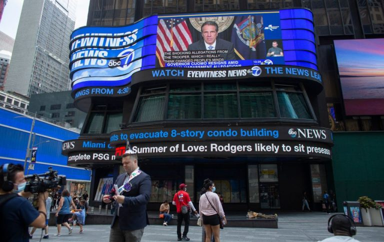 A screen shows news coverage of New York Governor Andrew Cuomo resigning over allegations of sexual harassment, in Times Square on August 10, 2021 in New York.