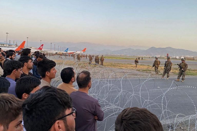 Afghans (L) crowd at the airport as U.S. soldiers stand guard in Kabul on August 16, 2021. Washington Post, relying on anonymous officials from both the U.S. and fallen Afghanistan governments, revealed the Biden administration declined an offer from the Taliban to secure Kabul after Afghan President Ashraf Ghani fled the country.
