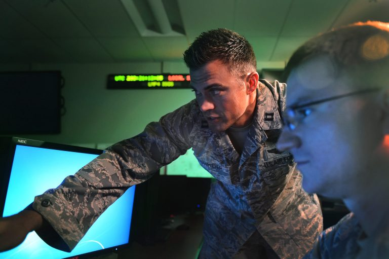 """Then-Capt. Matthew Lohmeier, 460th Operations Group Block 10 Chief of Training, instructs a trainee in the Standardized Space Trainer on July 22, 2015, at Buckley Air Force Base, Colorado. Lohmeier, now a Lt. Col., announced he is leaving the military effective Sept. 1 after being removed from his command post in May for criticising Marxist """"diversity, equity, and inclusion training"""" and Secretary of Defense Lloyd Austin on a podcast."""