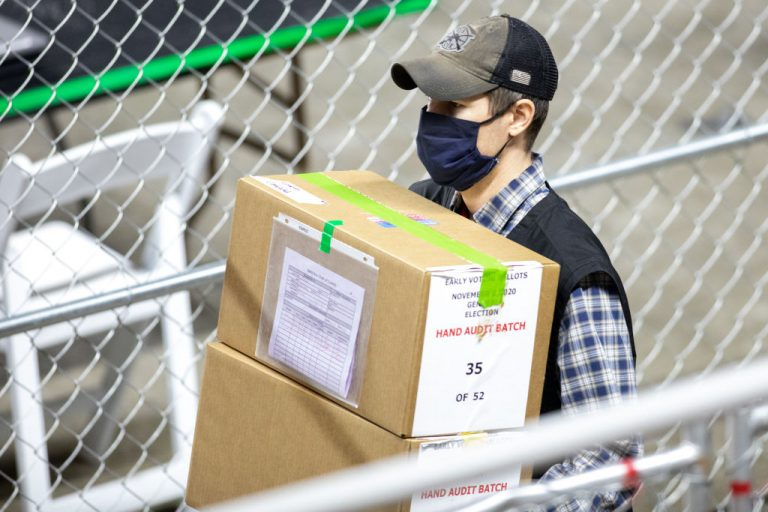 A contractor working for Cyber Ninjas, who was hired by the Arizona State Senate, transports ballots from the 2020 Presidential Election at Veterans Memorial Coliseum on May 1, 2021 in Phoenix, Arizona. The audit concluded Biden defeated Trump, but called into question serious issues with tens of thousands of ballots.