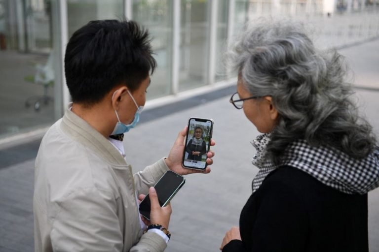 This photo taken on April 9, 2021 shows social media influencer and granny Ruan Yaqing (R) with assistant Xie Xincun (L) as they check a short video for her channel on video-sharing apps Kuaishou and Douyin - China's version of TikTok - in Beijing.