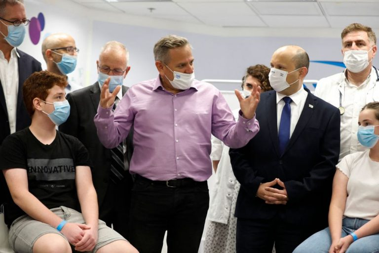 Israeli Prime Minister Naftali Bennett (2nd-R) listens as Health Minister Nitzan Horowitz (C) speaks during a visit to a Maccabi healthcare maintenance organisation outlet in a vaccine acceptance public relations photo in Tel Aviv on June 29, 2021. Horowitz was caught on a hot mic by Channel 12 TV telling a peer the country's vaccine passport system is for the purpose of pressuring vaccine acceptance and is not being properly enforced across the country