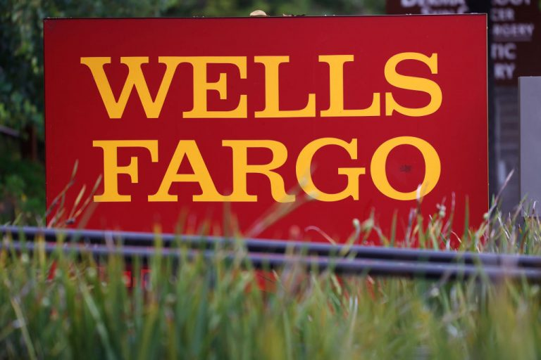 A sign is posted outside of a Wells Fargo bank.