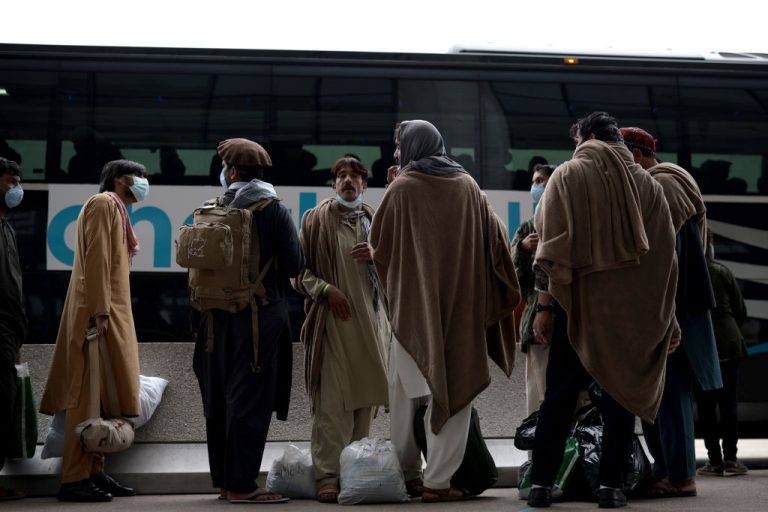 Afghan refugees board a bus at Dulles International Airport on August 31, 2021 in Dulles, Virginia. Two men, in unrelated events, were charged with sex crimes against minors and domestic violence while housed at Fort McCoy in Wisconsin. The base is holding almost 13,000 refugees, many of which have been given Visas and will soon be released into the community.