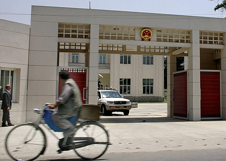 An Afghan man rides his bike outside the entrance to the Chinese embassy in Kabul on June 10, 2004.