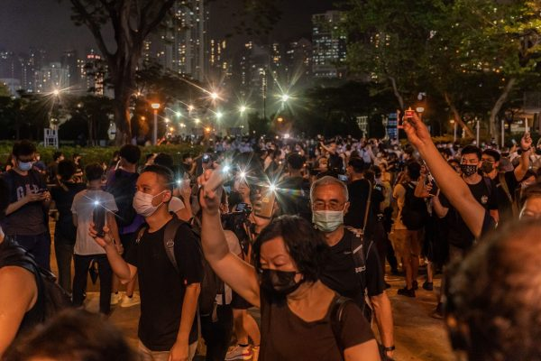 People hold up their phones with the light as they walk near Victoria Park after police closed the venue where Hong Kong people traditionally gather annually to mourn the victims of the Chinese Communist Party's 1989 Tiananmen Square Massacre in the Causeway Bay district on June 4, 2021, in Hong Kong.