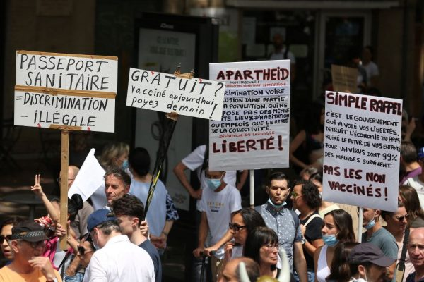 """Demonstrators hold up placards and banners, which read as """"Health Passport = Illegal Discrimination; Vaccine, Free today, but pay tomorrow; Apartheid, Freedom; Simple Reminder - no to vaccines"""" during a protest against vaccine passports, in Toulouse, France, on July 24, 2021."""