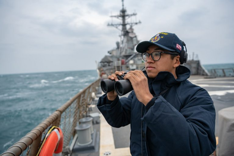 Seaman Xi Chan stands lookout on the flight deck as the Arleigh Burke-class guided-missile destroyer USS Barry (DDG 52) transits the Taiwan Strait during routine underway operations on April 23, 2020. Barry is forward-deployed to the U.S. 7th Fleet area of operations in support of security and stability in the Indo-Pacific region.