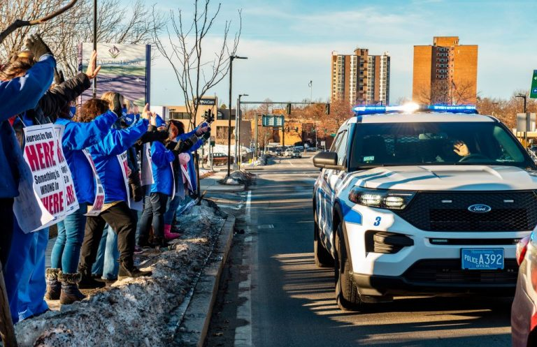 A police officer waves to and flashes his lights to Registered Nurses and supporters who are standing in a picket line as they wave to cars as they drive by outside St. Vincent Hospital in Worcester, Massachusetts on February 24, 2021. 800 Nurses voted to go on strike starting March 8 after giving the hospital a ten day notice. During the pandemic the nurses have cited more than 500 reports of safety issues for both themselves and patients and had more than 100 co-workers leave. Nurses are asking for increased staffing levels and a new contract.