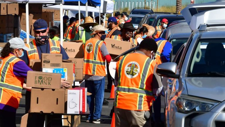 Los Angeles County Regional Food Bank workers help with food distribution to some 2,000 vehicles expected to arrive in Willowbrook, California, on April 29, 2021, in an ongoing effort to help people affected by the coronavirus pandemic.