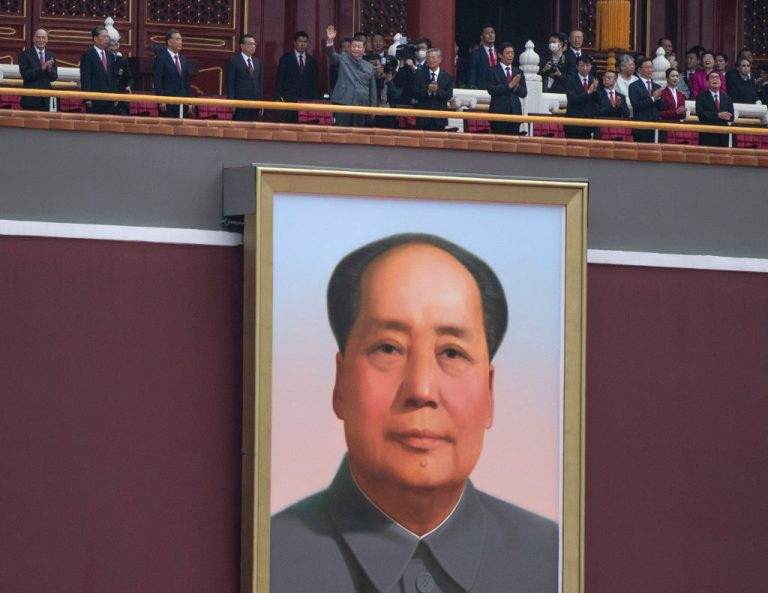 Chinese President and Chairman of the Communist Party Xi Jinping, top center, waves to the crowd after his speech above the portrait of the late Chairman Mao Zedong at a ceremony marking the 100th anniversary of the Communist Party.