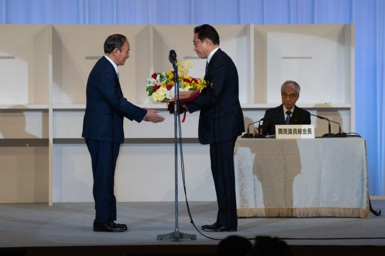 TOKYO, JAPAN - SEPTEMBER 29: Japanese outgoing Prime Minister Yoshihide Suga (L) receives a bouquet of flowers from former foreign Minister Fumio Kishida after Kishida was announced the winner of the Liberal Democrat Party leadership election on September 29, 2021 in Tokyo, Japan.