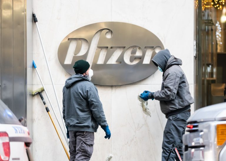 Workers clean the Pfizer logo in Murray Hill on December 21, 2020 in New York City. Project Veritas caught a trio of Pfizer scientists on hidden camera singing the praises of natural immunity over their company's vaccine, in addition to complaints of a corporate culture of surveillance, indoctrination, and profit.