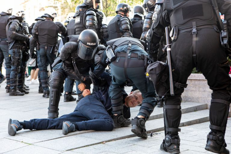 A man is restrained by police as demonstrators take part in a protest on September 10, 2021 in Vilnius, Lithuania against their government's Covid-19 policies, which include an attempt to introduce a mandatory health pass for access to cafes, shops, public transportation vehicles and other venues.