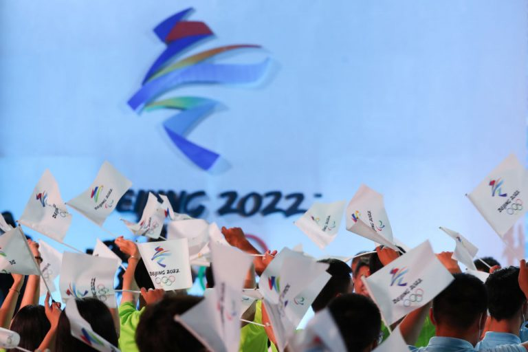 People wave flags of the Beijing 2022 Winter Olympic Games during the Beijing 2022 Winter Olympic & Paralympic Games Motto Launch Ceremony on September 17, 2021 in Beijing, China.