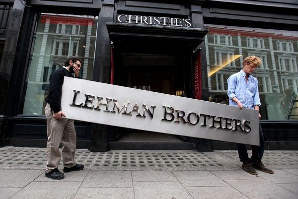 Two employees of Christie's auction house maneuver the Lehman Brothers corporate logo, which is estimated to sell for 3000 GBP and is featured in the sale of art owned by the collapsed investment bank Lehman Brothers on September 24, 2010 in London, England. Archegos Capital Management's head trader, William Tomita, was formerly a trader at the infamous firm who perished in the housing bubble. Archegos took big hits when Chinese stock fell after regulatory implementations on March 26.