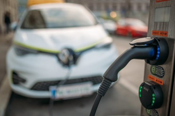 Close up of an electric vehicle charger in Vienna. Electric vehicles still command a major price premium over their combustion counterparts, have significant charging limitations, reduced capacity in cold weather, and electricity generation still primarily relies on the burning of fossil fuels such as coal and natural gas in many parts of North America.