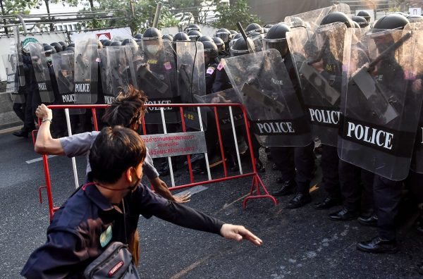 Thai pro-democracy protesters throw a barricade at riot police in Bangkok on February 1, 2021, close to where Myanmar migrants were demonstrating after Myanmar's military detained the country's de facto leader Aung San Suu Kyi and the country's president in a coup.