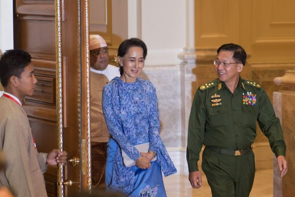 Aung San Suu Kyi (C) and the Myanmar military chief Senior General Min Aung Hlaing (R) arrive for the handover ceremony at the presidential palace in Naypyidaw on March 30, 2016. A close aide to Aung San Suu Kyi was sworn in as Myanmar's president on March 30, a role that will see him act as a proxy for the pro-democracy figurehead and carry the hopes of a nation emerging from military rule.