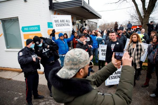 Protesters and Police officers gather at Adamson Barbecue, an Etobicoke business that has defied provincial shutdown orders, in Toronto, Canada, on November 25, 2020. Owner Adam Skelly said he had nothing left to lose by re-opening, due to financial distress caused by Premier Doug Ford's constant lockdown measures.