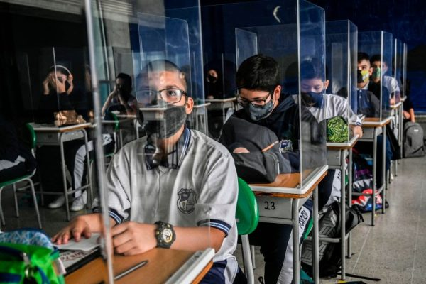 Students take part in a class while partitioned by plexiglass at the Antonio Jose Sucre Public School, amid the COVID 19 pandemic in Itagui, Colombia on February 25, 2021.