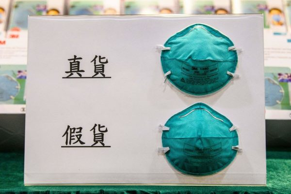 Examples of a real (top) and fake (bottom) mask are shown on a display board during a press conference at the Customs Headquarters Building in Hong Kong on October 30, 2020. Fake 3M masks were seized in addition to counterfeit vaccines by South African police.