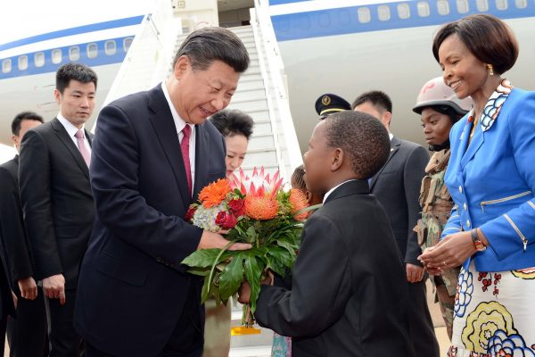 """Chinese state media often share photos of Chinese leader Xi Jinping laughing and intimately interacting with the """"ordinary person,"""" especially in its claimed battle against Chinese poverty. Here, Xi accepts flowers from a schoolboy after arriving at Air Force Base Waterkloof in South Africa on Dec. 2, 2015."""
