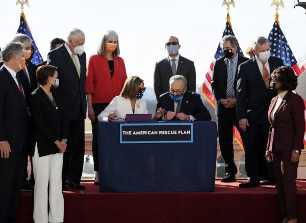 Speaker of the House Nancy Pelosi and Senate Majority Leader Chuck Schumer sign the American Rescue Plan Act after the House Chamber voted on the final revised legislation of the $1.9 trillion spending plan, at the U.S. Capitol on March 10, 2021, in Washington, DC. Jared Golden of Maine was the only Democrat to vote nay on the bill.