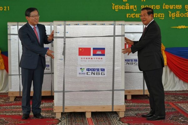 China's ambassador to Cambodia Wang Wentian (L) hands over a shipment of Sinopharm Covid-19 coronavirus vaccine to Cambodian Prime Minister Hun Sen (R) during a ceremony at Phnom Penh International Airport in Phnom Penh on February 7, 2021. The CCP's offer to supply Olympic vaccines has been rejected by the Japanese government.